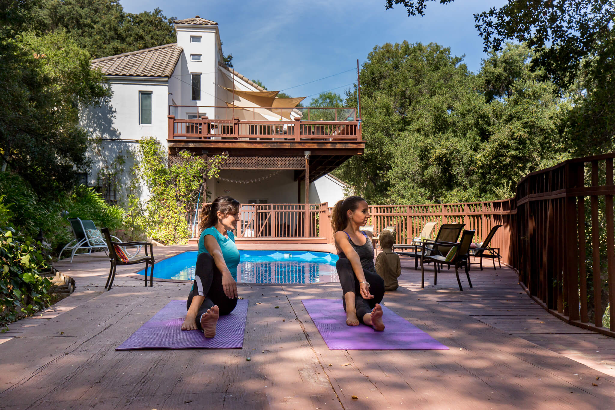 Clients do yoga by the pool at Canon House