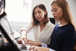 Two teen girls play piano as an example of how does music therapy work
